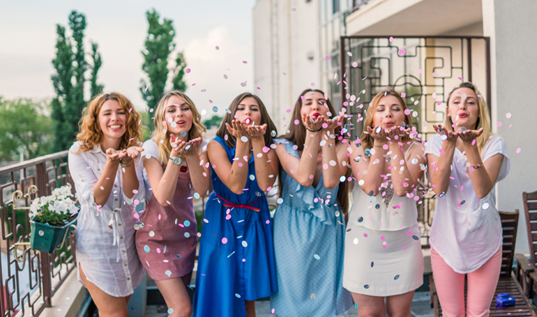 line of girls blowing confetti