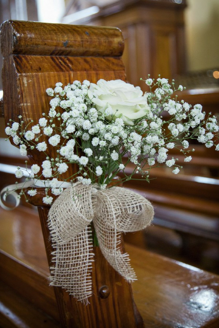 baby's breath bouquets with burlap bows hanging from pew for wedding