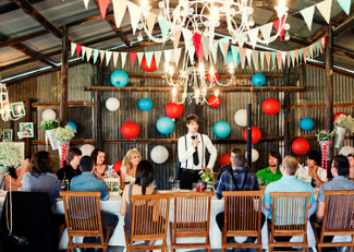 groom at barn wedding with bunting decorations