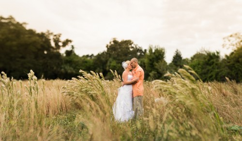 bride and groom in meadow at rustic wedding